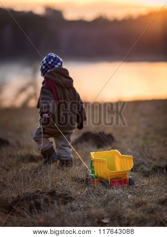 Little Boy Playing Outdoor With A Toy Car.