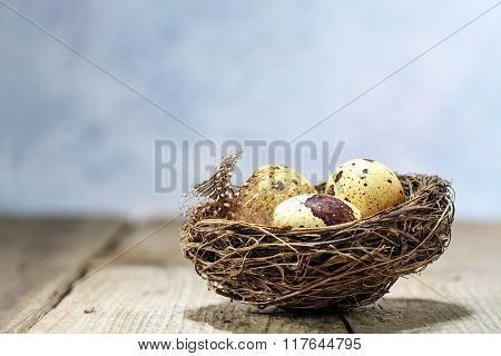 Nest With Tree Eggs On A Rustic Vintage Table, Bright Blue Background With Copy Space