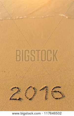 2016 - inscription on sand beach with the soft wave.