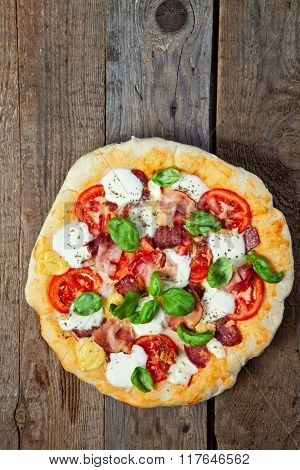 Pizza with salami, tomato and ham