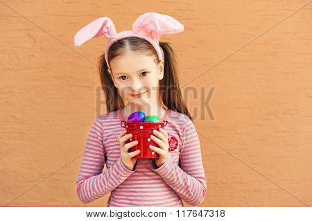 Cute little girl wearing rabbit ears, holding bucket with colorful easter eggs