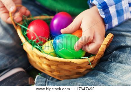Small basket with colorful easter eggs in baby's hands