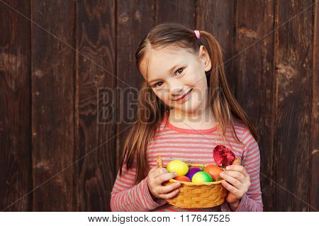 Cute little girl holding small basket with colorful easter eggs