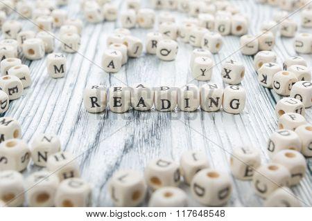 READING word written on wood block. Wooden Abc