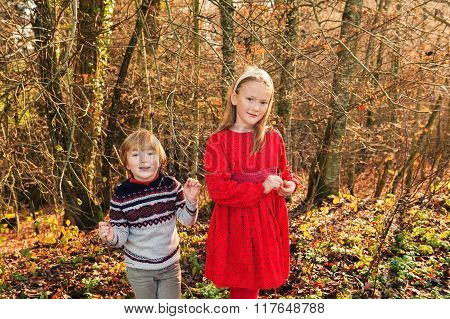Two adorable kids plying in autumn forest on a warm sunny day