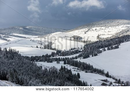 nice winter landscape in mountains wit dark sky over
