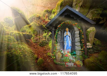 Our Lady of Lourdes (Virgin Mary) on place of wonders, wishing well in deep Bohemian forest (Konstantinovy Lazne) near Karlovy Vary, Czech Republic. Amazing European landmark. Warm filtered picture.