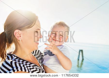 Little boy in mothers arms, sunny day by the water