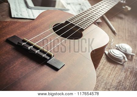 Ukulele Guitar With Earphone On Wooden Table