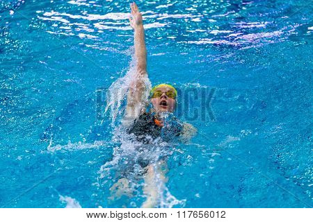 young female athlete swimming backstroke in sprint distance in pool