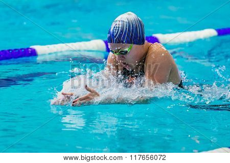 young female athlete swimming breaststroke in pool