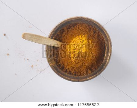 turmeric powder in a wooden bowl on the white background