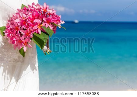bright tropical flower bouquet in hands of young beautiful bride on blue beach and sea background