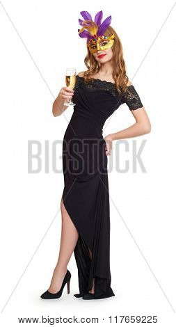 Young woman in black evening gown on white. Carnival mask on face. Wineglass champagne in hands.