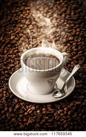 Hot coffee with beans background with spoon