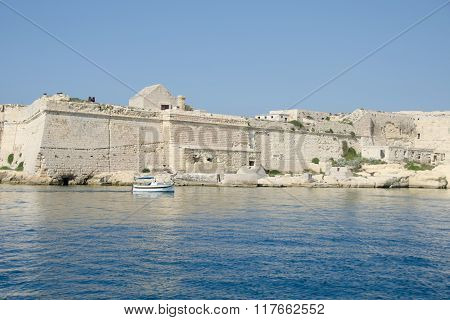 A Small Boat Sails Past The Walls Of The Ancient City