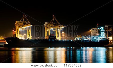 Cargo Ship Unloading The Container At Port During The Night Time