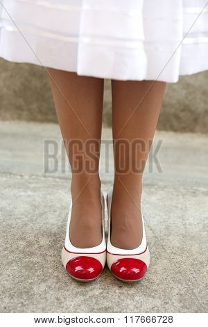 Women's legs in beige delicate tights with retro shoes
