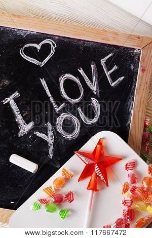 I love you, written on a blackboard with chalk, caramel, candy, star, wand, valentines day, valentin
