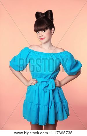 Hairstyle. Beautiful Smiling Girl With Bow Hair Posing In Blue Dress Isolated On Studio Background.