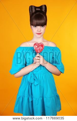 Heart Lollypop. Beautiful Teen Girl With Colourful  Lolli Pop. Funny Teenage With Bow Hairstyle Isol
