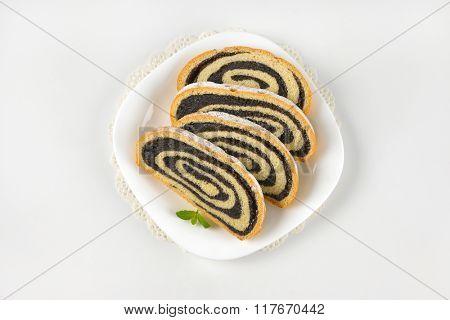 sliced poppy seed roll on white plate