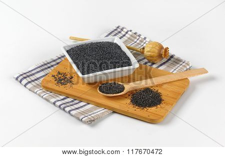 bowl of poppy seeds na poppy head on wooden cutting board