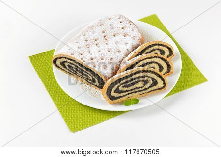 sliced poppy seed roll on white plate and green place mat