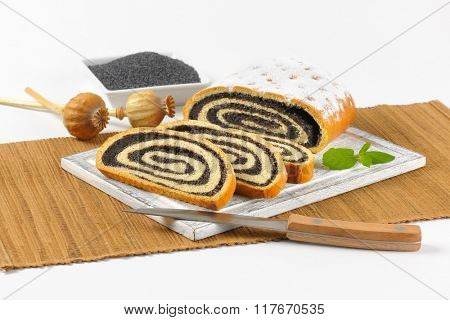 bowl of poppy seeds and sliced poppy seed roll on wooden cutting board