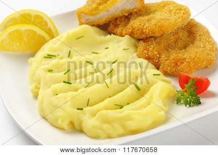 close up of mashed potato puree with chopped chives and breaded turkey breast on white plate