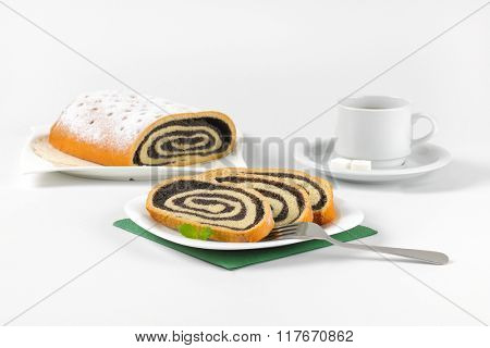 sliced poppy seed roll and cup of coffee on white background