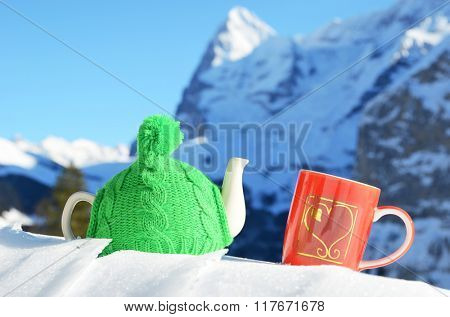 Tea pot in the knitted cap and red cup with a heart in the snow