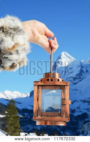 Lantern in the hand against mountain peak