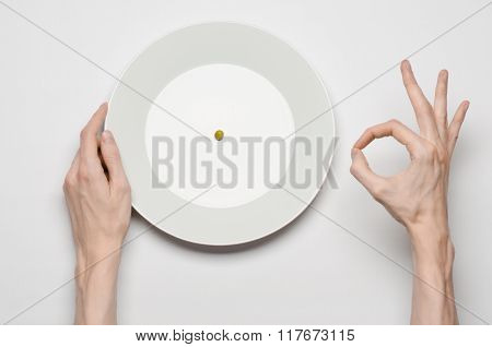 Healthy Food Theme: Hands Holding Knife And Fork On A Plate With Green Peas On A White Table Top Vie