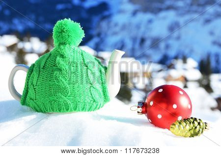 Tea pot in the cap against alpine scenery