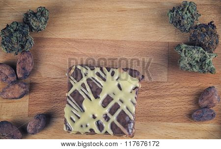 Weed brownie over wood background with cannabis buds and cacao beans