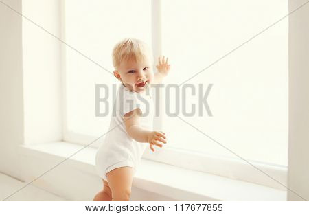 Little Smiling Baby In White Room At Home Stands Near Window