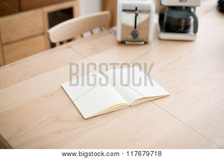 Open square format brochure on a wooden table