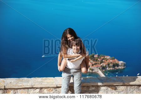 Happy Couple In Love Summer Vacations. Young Man Piggybacking His Beautiful Girlfriend Over Sea, Whi