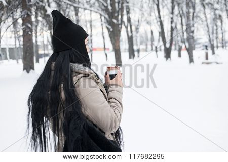 Young woman with long black hair outoors in winter holding coffee cup