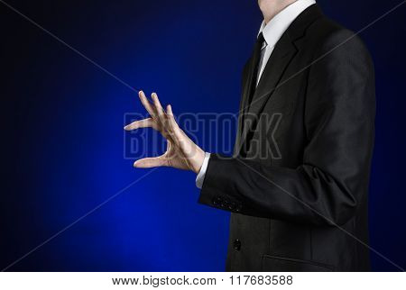 Businessman And Gesture Topic: A Man In A Black Suit And White Shirt Shows A Hand Pinch On A Dark Bl