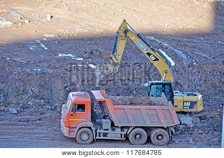 Excavator Loads The Truck Body With Large Clods Of Earth During Construction Works At The Building S