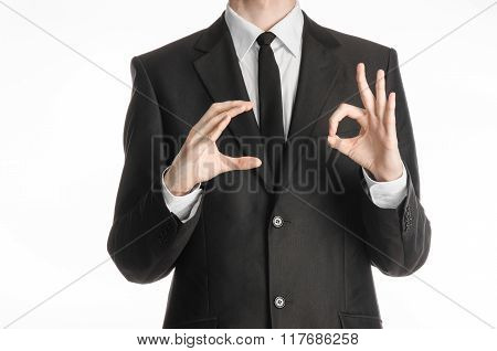 Businessman And Gesture Topic: A Man In A Black Suit And Tie Holds His Right Hand And The Left Shows