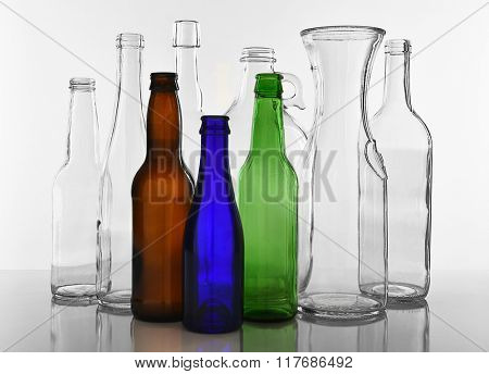 Empty Glass bottles on white with reflection. Clear glass and colored bottles.