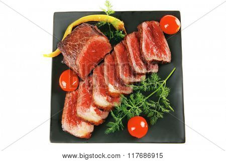 meat pepper and tomatoes on dark plate
