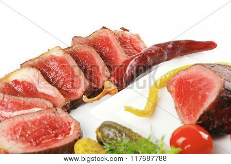 meat sliced with tomatoes and peppers on white