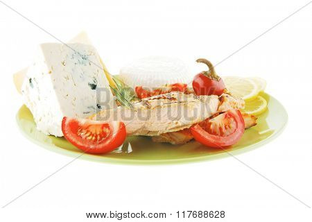 french cheeses and salmon with vegetables on green plate