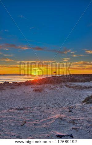 Ventura sunset across the wavy sand.