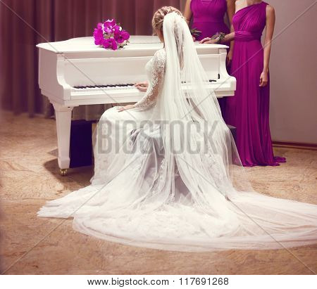 Beautiful Bride In Wedding Dress And Bridesmaids. Fashion Elegant Girl With Long Veil Sitting On Whi