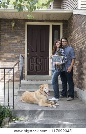 couple on steps of new home purchase